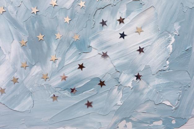 Estrellas de confeti de lámina de plata de moda sobre fondo blanco y azul. Foto Premium