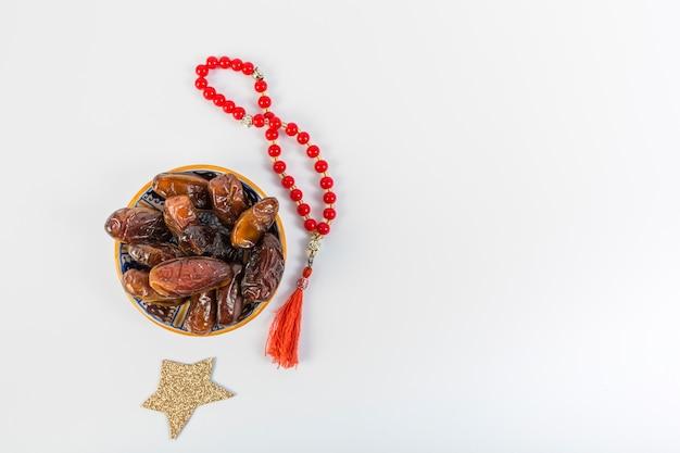 Estrellas doradas con tazón de dátiles jugosos y cuentas de rezo rojas sobre fondo blanco Foto gratis