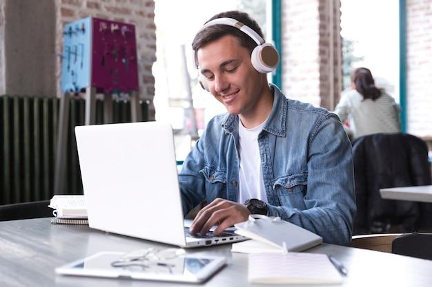 Estudiante adolescente en auriculares sentado en la mesa y escribiendo en el cuaderno Foto gratis