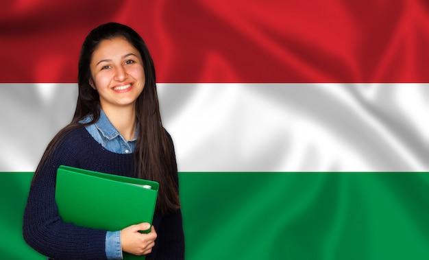 Estudiante adolescente sonriendo sobre bandera húngara Foto Premium