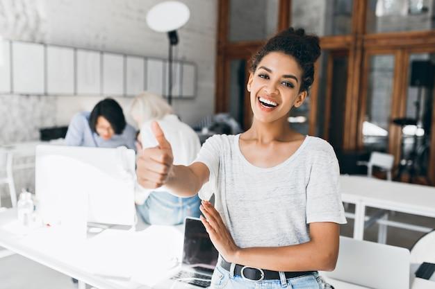 Estudiante africana alegre con peinado corto sosteniendo el pulgar hacia arriba después de aprobar los exámenes. retrato de mujer negra feliz en camiseta gris divirtiéndose en la oficina mientras sus colegas trabajan en el proyecto. Foto gratis