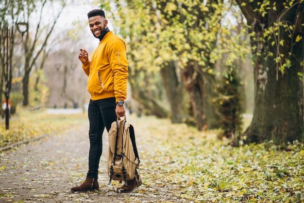 Estudiante afroamericano caminando en el parque Foto gratis
