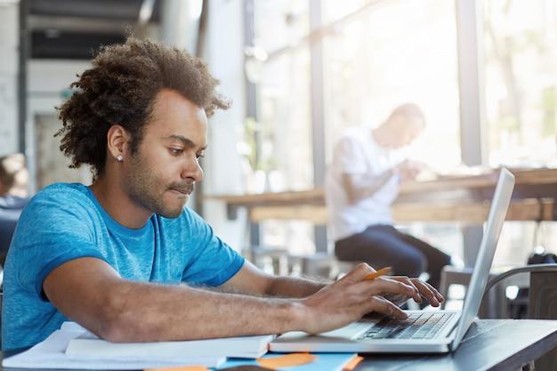 Estudiante afroamericano elegante mecanografía en la computadora portátil mientras está sentado en la mesa de café con libros de texto, trabajando en la tarea, habiendo enfocado mirada concentrada. personas, tecnología moderna y educación Foto gratis