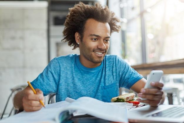Estudiante afroamericano feliz en la cafetería rodeado de libros y copias de libros preparándose para las clases escribiendo mensajes de texto en un dispositivo electrónico sonriendo agradablemente mientras lee sms Foto gratis