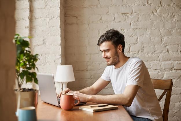 Estudiante atractivo usa tecnología de internet y conexión wi-fi de alta velocidad para chatear con un amigo Foto gratis