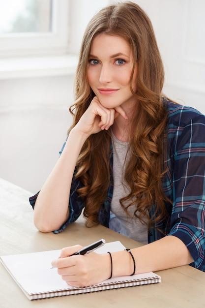 Estudiante. chica atractiva junto a la mesa Foto gratis