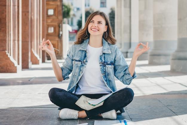 Estudiante chica sentada en el suelo y meditando. lovely girl pide una buena nota en el examen. niña reza en posición de loto. Foto Premium