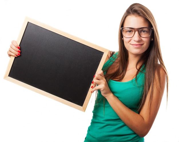 Estudiante con gafas sujetando una pizarra Foto Gratis