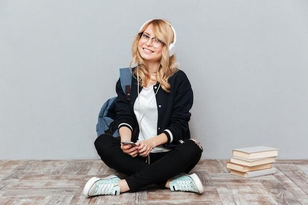 Estudiante escuchando música en el piso Foto gratis