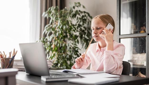 Estudiante hablando por teléfono en casa Foto gratis