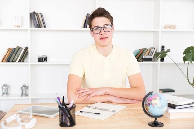 Estudiante inteligente en copas sentado en el escritorio Foto gratis