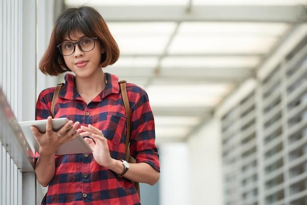 Estudiante inteligente con gafas usando la aplicación móvil en el teclado digital Foto gratis