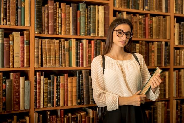 Estudiante inteligente con el libro en la biblioteca Foto gratis