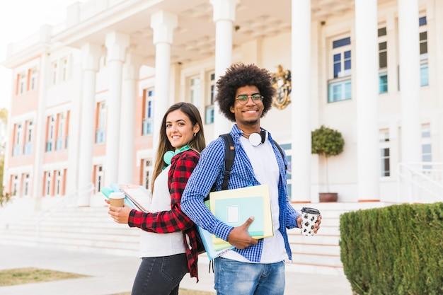 Estudiante masculino y femenino joven diverso que sostiene los libros y la taza de café para llevar que se coloca delante del edificio Foto gratis