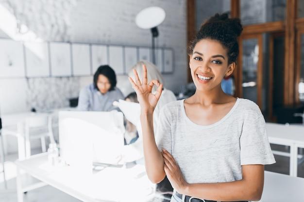 Estudiante mulata rizada posando con sonrisa y signo bien después de una prueba difícil en la universidad internacional. retrato interior de mujer africana trabaja como gerente en la oficina con un joven asiático detrás. Foto gratis