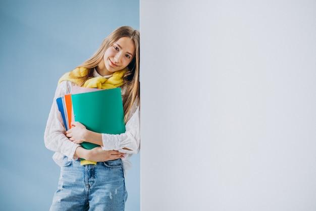 Estudiante de pie con carpetas coloridas Foto gratis