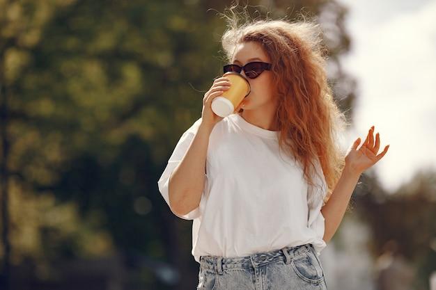 Estudiante de pie en una ciudad con una taza de café Foto gratis