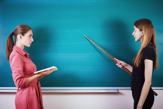 Estudiante con profesor de pie en el aula en el pizarrón. día del maestro. Foto Premium