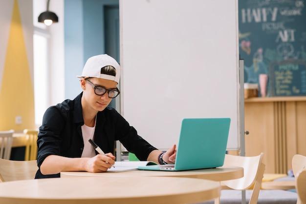 Estudiante que trabaja con la computadora portátil Foto gratis