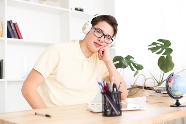Estudiante relajado sentado en auriculares Foto gratis