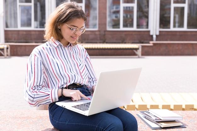 Estudiante universitario con laptop y cuadernos Foto gratis