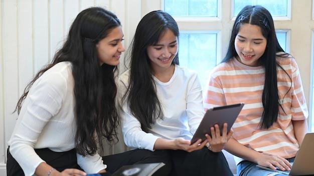 Estudiante universitario que hace un grupo de e-learning usando una tableta de computadora y sentados juntos en el piso de la sala de estar Foto Premium
