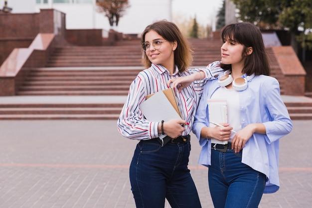 Estudiantes adolescentes en camisas ligeras de pie con libros. Foto gratis