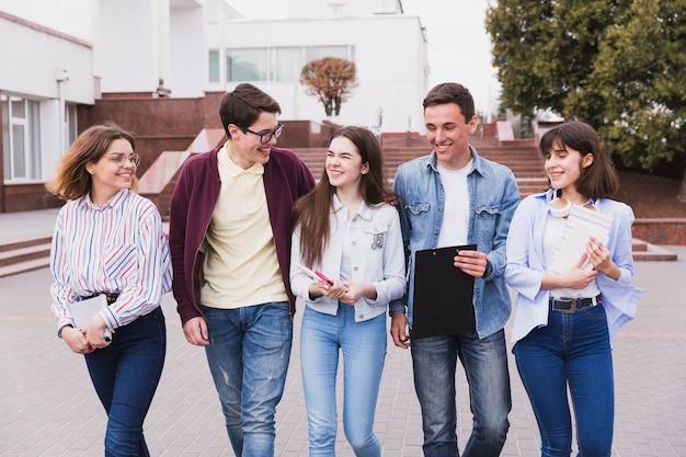 Estudiantes adolescentes riendo y caminando con libros. Foto gratis