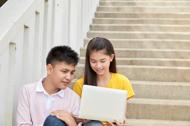 Los estudiantes adolescentes trabajan en el trabajo escolar en la computadora portátil Foto Premium