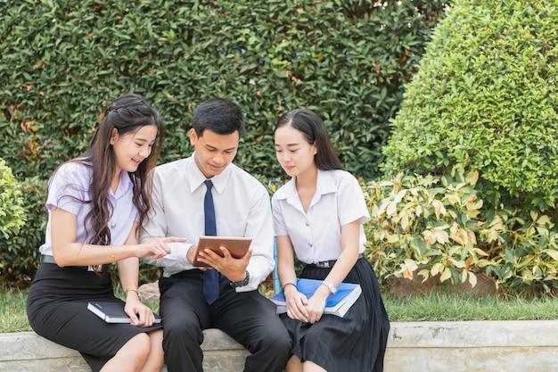 Estudiantes asiáticos usando tableta para hacer tarea Foto Premium