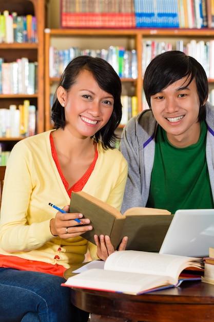 Los estudiantes en la biblioteca son un grupo de aprendizaje. Foto Premium