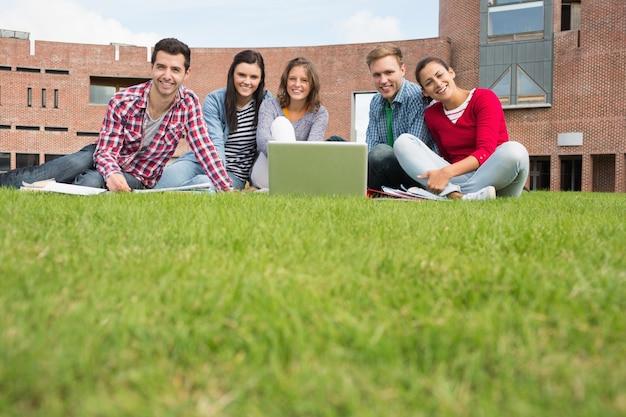 Estudiantes con la computadora portátil en el césped contra el edificio de la universidad Foto Premium