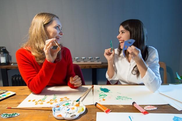 Estudiantes de la escuela de arte asombrados trabajando con plantillas Foto gratis
