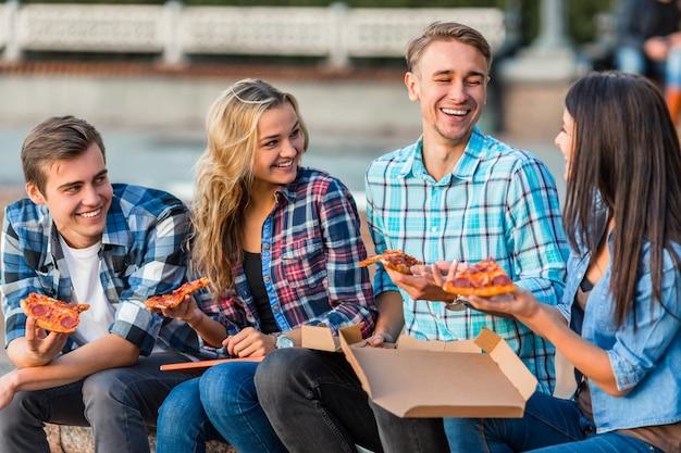 Los estudiantes jóvenes divertidos, están comiendo pizza grande. Foto Premium