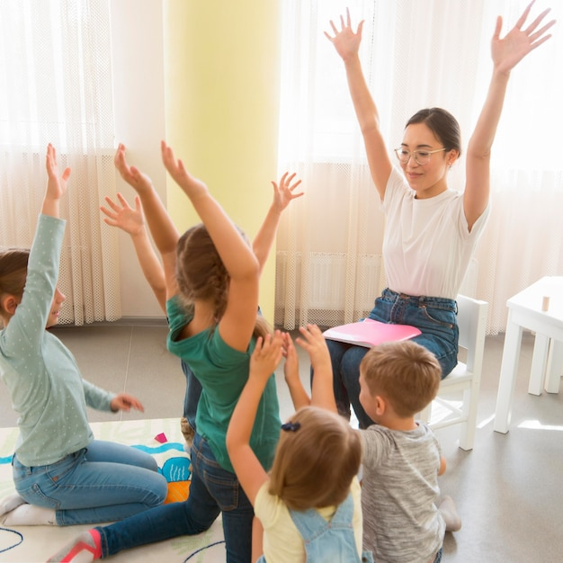 Estudiantes jugando con su maestra de jardín de infantes. Foto gratis