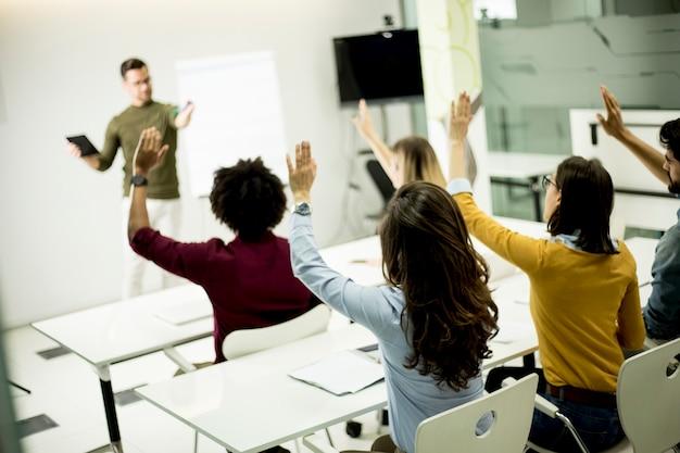 Estudiantes levantando la mano para responder a la pregunta durante el taller de capacitación. Foto Premium