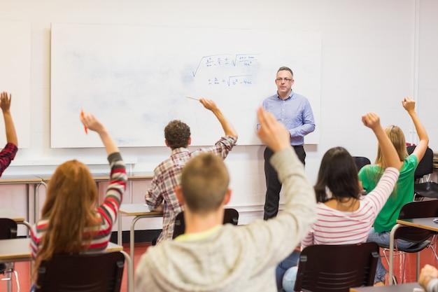 Estudiantes levantando las manos en el aula | Foto Premium