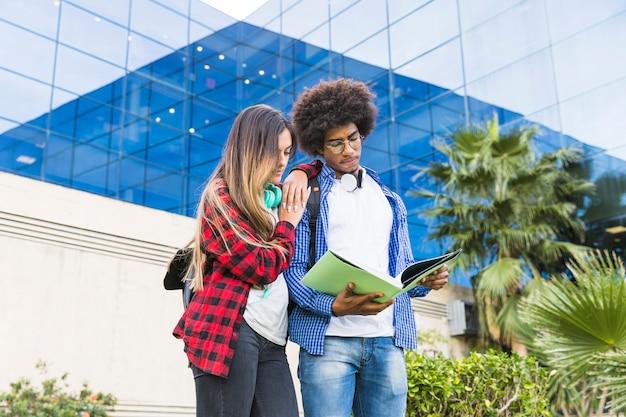 Estudiantes masculinos y femeninos adolescentes que leen el libro de pie contra el edificio de la universidad Foto gratis