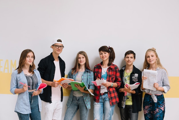 Estudiantes de pie con los cuadernos Foto gratis
