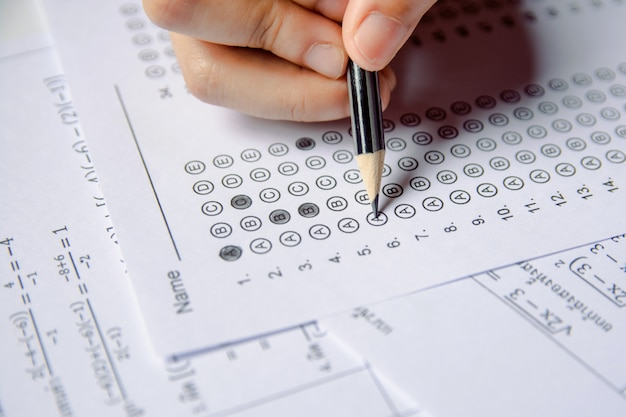 Estudiantes que sostienen a lápiz la escritura de la opción seleccionada en las hojas de respuestas y las hojas de preguntas de matemáticas Foto Premium