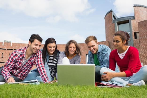 Estudiantes que usan la computadora portátil en césped contra la construcción de la universidad Foto Premium