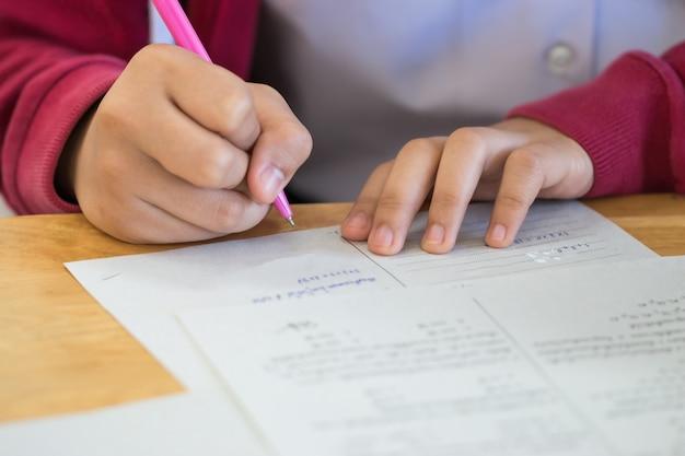 Los estudiantes que usan información de escritura con lápiz en papel de respuesta blanco en la escuela secundaria, sala de exámenes asiáticos, pruebas o examen es una evaluación destinada a medir el conocimiento, la habilidad, la aptitud, el concepto de educación Foto Premium