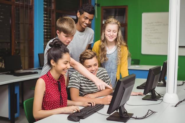 Estudiantes sonrientes que estudian en el aula de informática Foto Premium