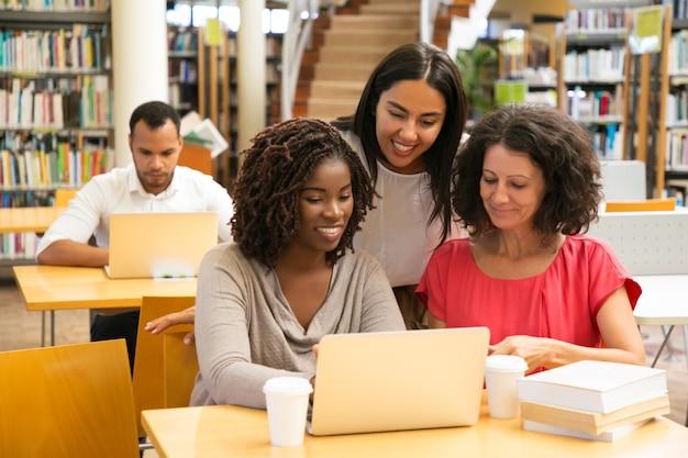 Estudiantes sonrientes que trabajan con la computadora portátil en la biblioteca Foto gratis