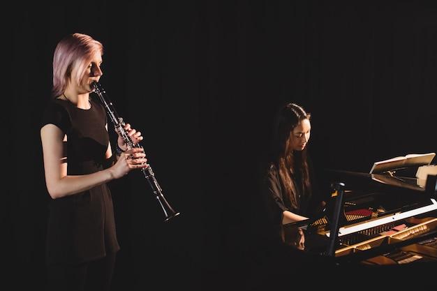 Estudiantes tocando clarinete y piano Foto gratis