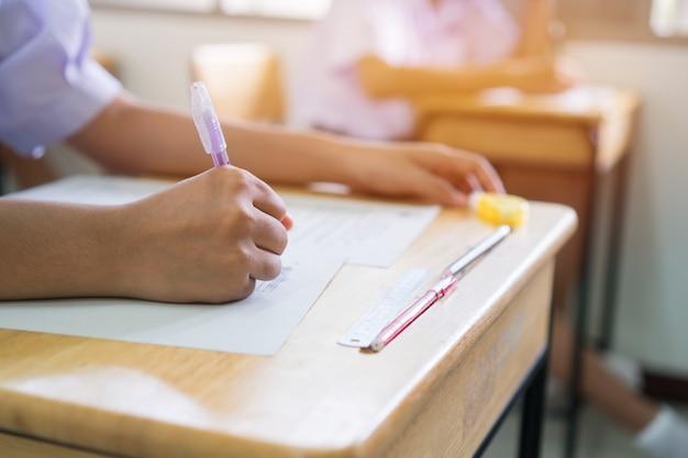 Estudiantes uniformes de educación que examinan el examen con un lápiz para exámenes de selección múltiple o examen de evaluación Foto Premium