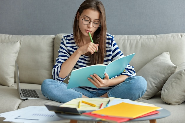 Estudiar el concepto en línea. mujer joven seria que está ocupada con un proyecto independiente remoto, se sienta en un cómodo sofá, escribe notas, sostiene un libro de texto, usa una computadora portátil en casa con internet inalámbrico Foto gratis