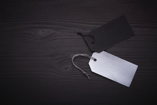 Etiquetas en blanco negras y plateadas en madera negra. Foto Premium