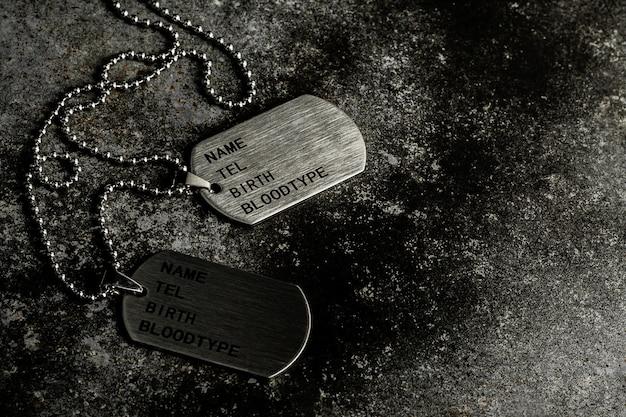 Etiquetas de perro militares en blanco en la placa de metal oxidada abandonada. Foto Premium