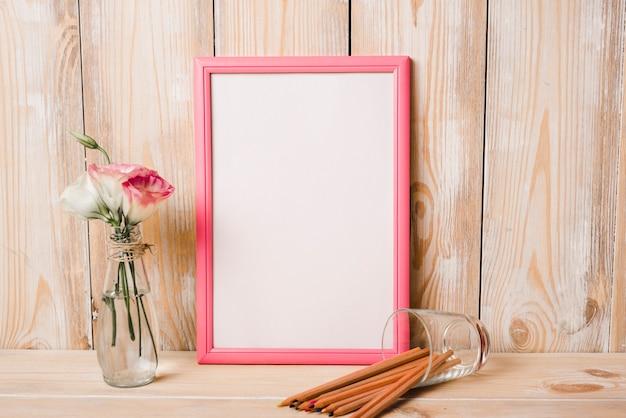 Eustoma en florero de vidrio; lápices de colores y marco de fotos blanco con borde rosa en mesa de madera Foto gratis